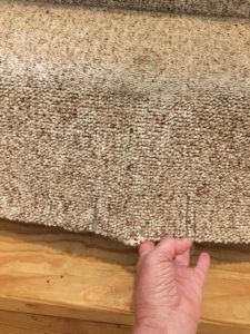 A picture of my hand pulling away the carpet from stairs