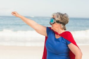 Picture of older woman wearing a superwoman cape, widows try to be superwomen